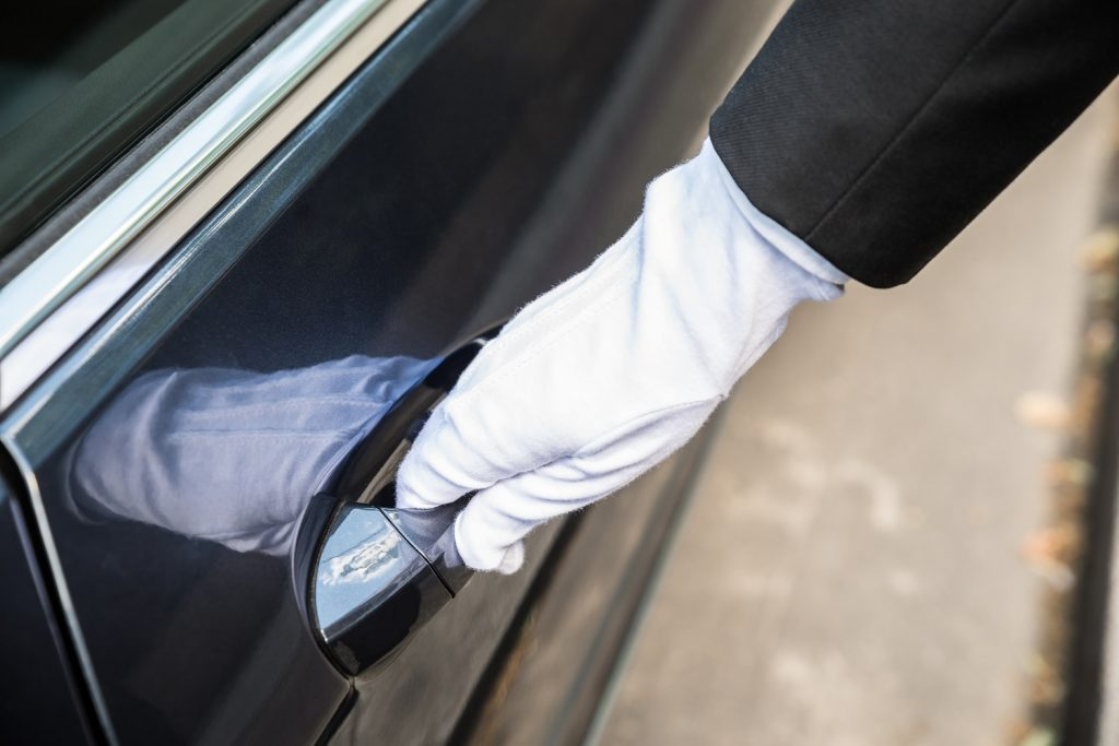 Male Chauffeur Opening Door Of Car