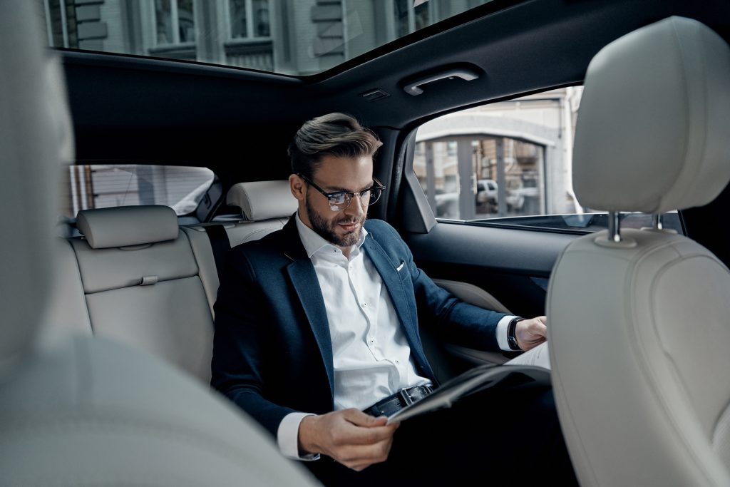 businessman reading news while in chauffeured car