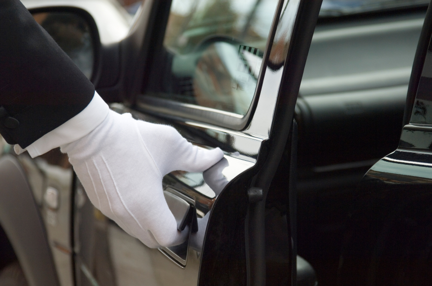 chauffeur's gloved hand opening luxury car